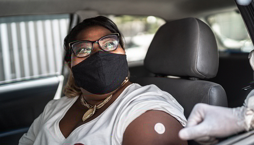 Woman in mask in car getting a covid test